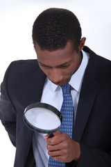 Curious man inspecting an object with a magnifying glass