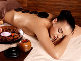 Fototapety woman having stone massage in spa salon
