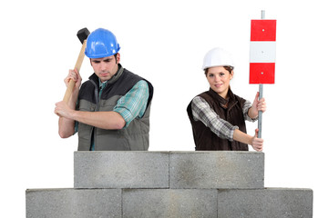 Man and woman working on wall