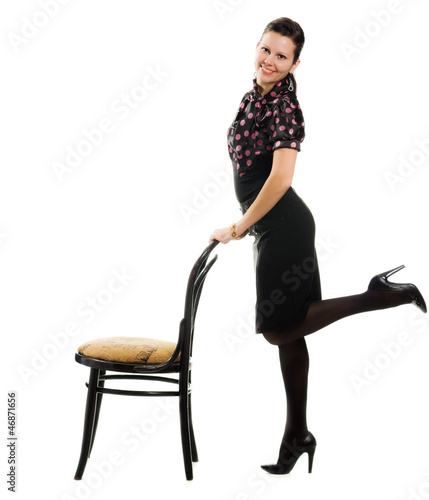 Pretty happy retro woman standing with a chair.