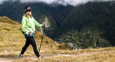 Woman hiker nordic walking in mountains