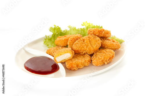 Plate of nuggets with dip sauce, one nugget cut