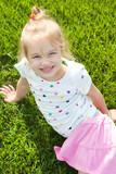Cute little girl on the green grass