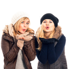Happy women in winter clothes sending kiss