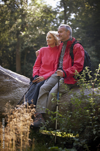 A mature couple sitting on a tree trunk resting