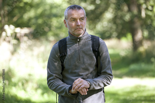 A portrait of a mature man standing in the countryside