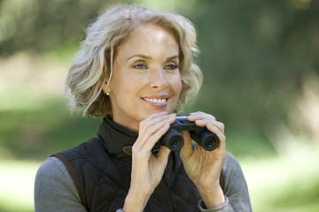 A mature woman outdoors, holding a pair of binoculars