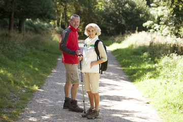 A mature couple standing on a country path, smiling