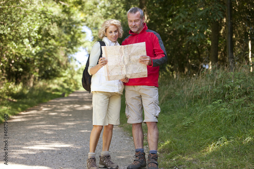 A mature couple walking in the countryside looking at a map