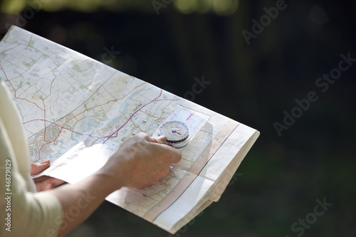 A woman holding a map and compass, close up
