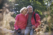 A mature couple sitting on a tree trunk