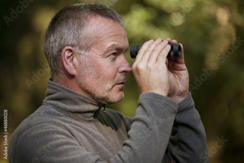 A mature man looking through a pair of binoculars