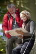 A mature couple standing in woodland looking at a map, close up