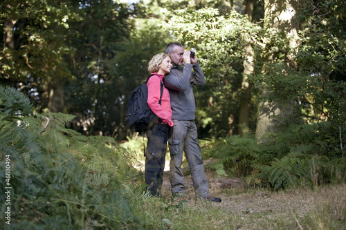 A mature couple looking through binoculars in the countryside