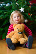 little girl in front of christmastree