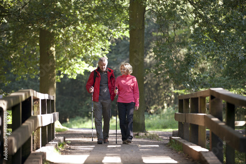 A mature couple walking over a footbridge in the countryside