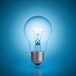 Leinwanddruck Bild - light bulb on blue background.