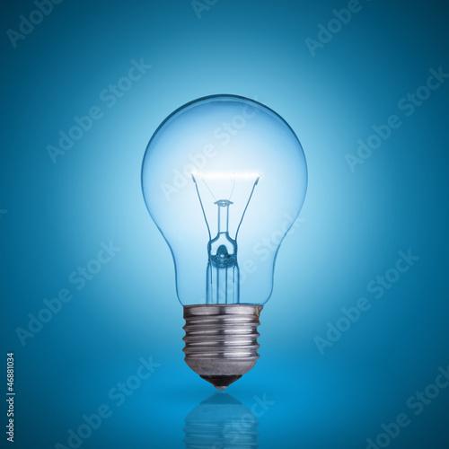 Leinwanddruck Bild light bulb on blue background.