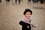 stylish, thoughtful boy in a black coat and hat with a beautiful