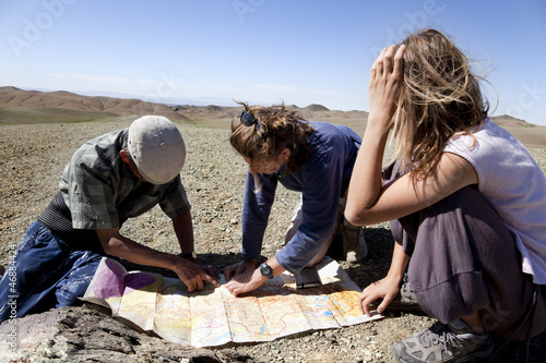 two girls and a man looking at a map of the Gobi desert