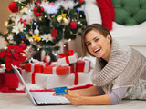 Woman with laptop near Christmas tree making online purchase