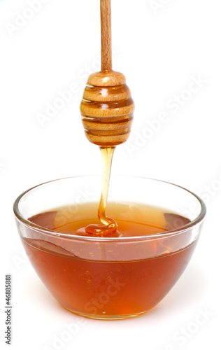 Honey dripping from a wooden honey dipper on white background