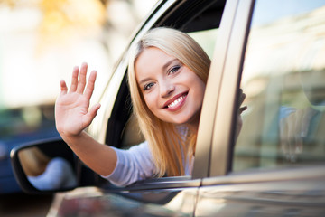 Young woman waving from car window