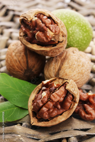 walnuts with green leaves, on  wicker background
