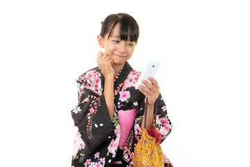 携帯を持つ浴衣を着た女の子