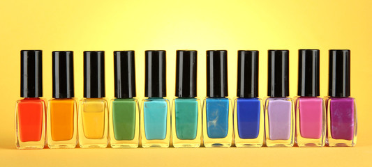 Group of bright nail polishes, on yellow background