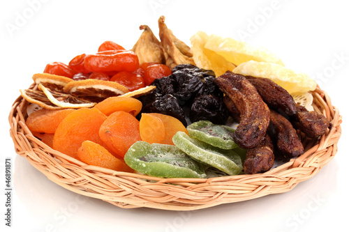 Dried fruits on wicker plate isolated on white