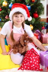 Little girl in Santa hat near the Christmas tree in festively