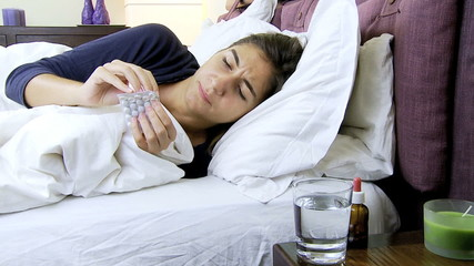 Sick woman in bed taking aspirin