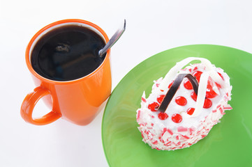 Cup of coffee and sweet cake on a green plate