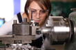 Junge Frau an Drehmaschine