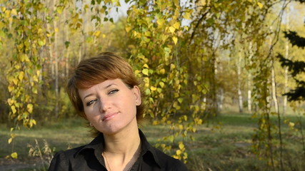 Young woman standing under a birch in autumn park and smiling