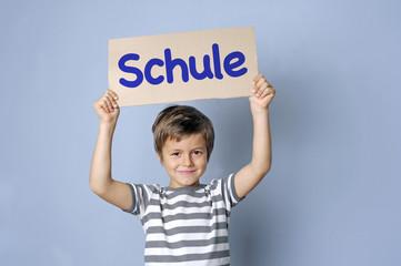 """Kind hält Schild hoch mit Typo """"Schule"""""""