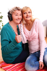 Granny and granddaughter listening music