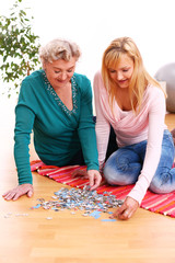 Granny and granddaughter playing puzzle