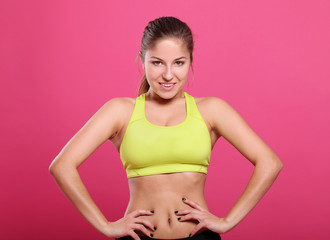 Attractive fitness girl over a purple background