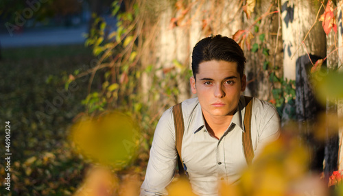 Handsome young man  in fall (autumn) near wooden fence