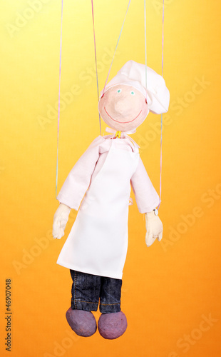 Wooden puppet as cook on orange background