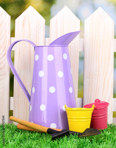 gardening tools on green grass on wooden fence background