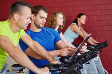 Fitnesstrainer redet mit Mann beim Spinning