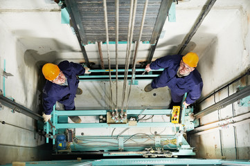 machinists adjusting lift in elevator hoistway