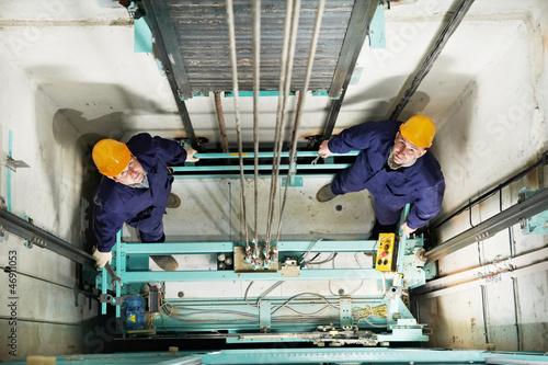 Leinwanddruck Bild machinists adjusting lift in elevator hoistway