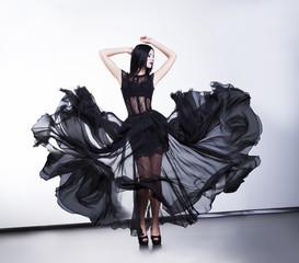 Fantastic fashion woman in fluttering black transparent dress