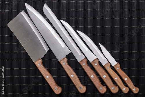 set of kitchen knifes on black mat