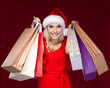 Pretty girl in Christmas cap hands shopping packets