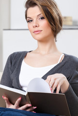 Attractive woman reads the book sitting on the white sofa